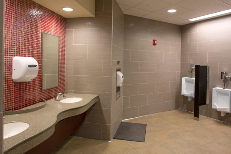 a public building modern bathroom with small red tile above sinks and large format wall tiles