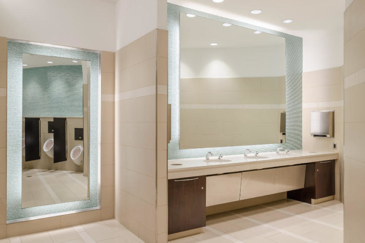 a commercial building public bathroom with an elegant design with small glass wall tiles around large mirrors and large floor tiles
