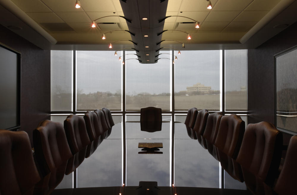 a boardroom with a shiny granite conference table in the middle and dim lights above