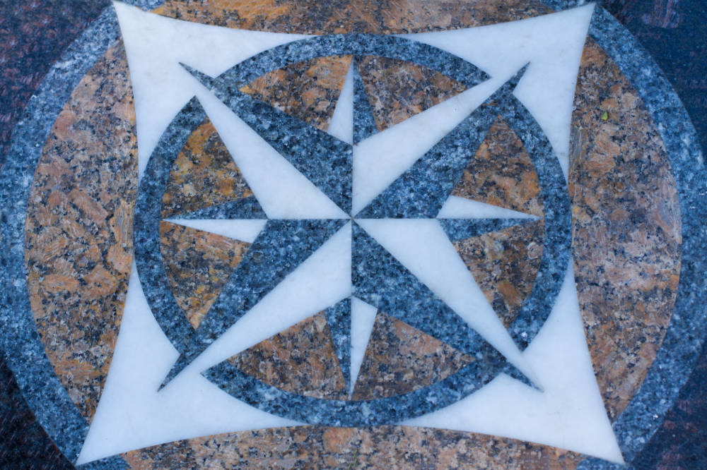 a geometric star-shaped floor medallion made of granite and marble for a commercial building entry