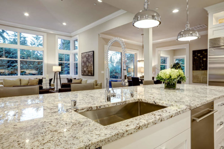 a large kitchen island with a clean light color granite countertop