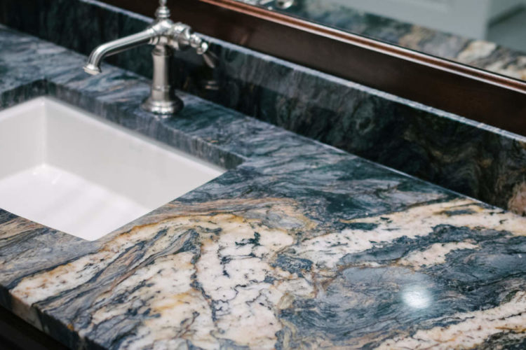 a closeup of a clean bathroom vanity countertop made of granite